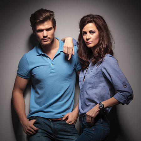 Fashion couple leaning on a grey wall while looking at the camera, the man is holding his hands in pockets, while the woman is leaning on him. photo