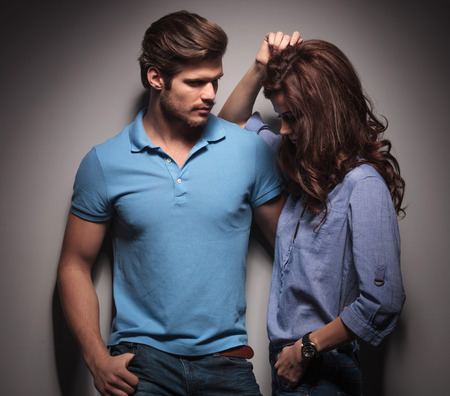 Handsome muscular fashion man looking at his lover, holding her while she is leaning on him, looking down. photo