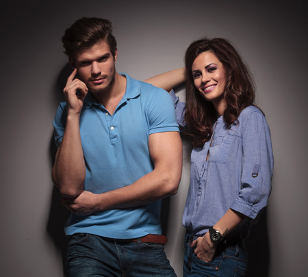 Beautiful fashion woman leaning on her lover while he is holding his finger to his cheekbones. Against a grey wall. photo