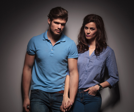 Cute fashion couple looking at the camera while leaning on a grey wall, holding hands. photo