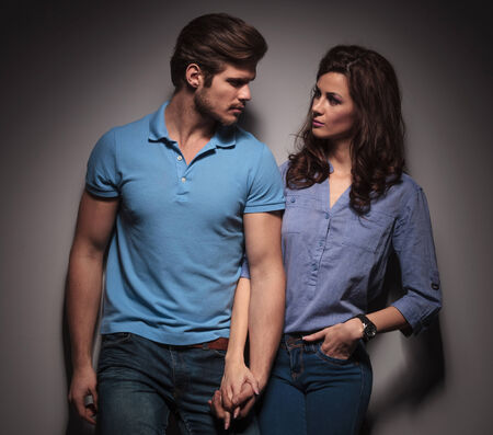 In love fashion couple looking at each other while holding hands, leaning on a grey wall. photo