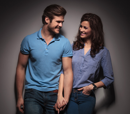 Happy fashion couple leaning on a grey wall while holding hands and looking at each other. photo