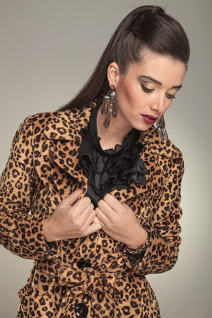 Fashion woman wearing a animal print coat, fixing her collar while looking down. photo