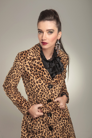 Fashion woman wearing a animal print coat looking at the camera while fixing her coat. photo