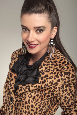 Close up picture of a elegant fashion woman in animal print coat smiling for the camera. photo