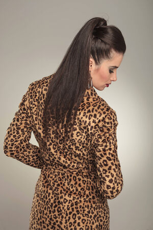 Rear view of a young fashion woman wearing a animal print coat, looking down. photo