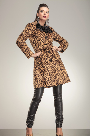 Full body image of a beautiful fashion woman in animal print coat posing for the camera. photo