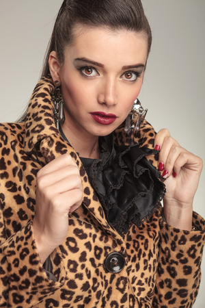 Close up portrait of young fashion woman pulling her collar while looking at the camera. photo