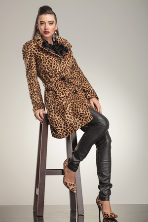 Beautiful young fashion woman in animal print coat and leather pants, sitting on a stool. photo