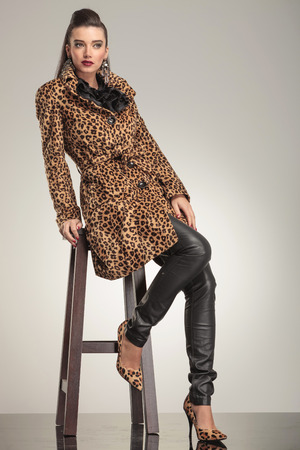 Full body picture of a young fashion woman sitting on a stool, looking away from the camera. photo