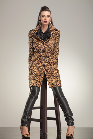 Full length picture of a young fashion woman sitting on a stool, on studio background. photo