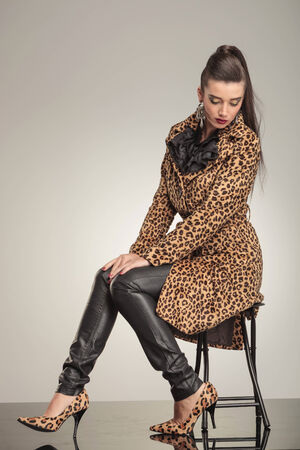 Young fashion woman looking down while sitting and resting her hands on her knees. photo