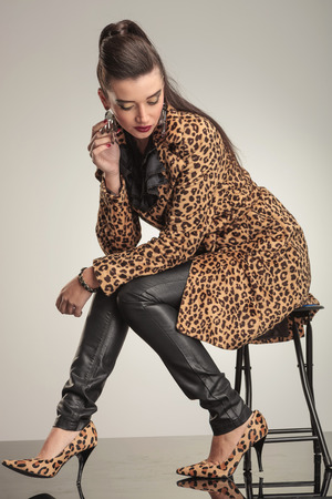 Young fashion woman looking down while sitting on a stool, playing with her earring. photo