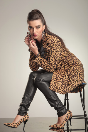 Fashion woman playing with her earring while sitting on a stool. photo