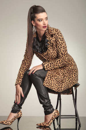 Young fashion woman sitting on a stool holding her hand to her ankle, looking away. photo