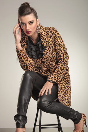 Fashion woman sitting on a stool holding one hand to her forehead, looking at the camera. photo