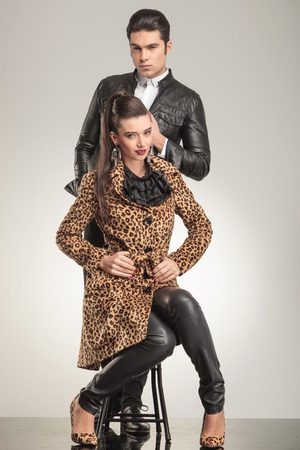 Handsome young man looking at the camera, pulling his leather jacket while his girlfriend is sitting on a stool fixing her coat. photo