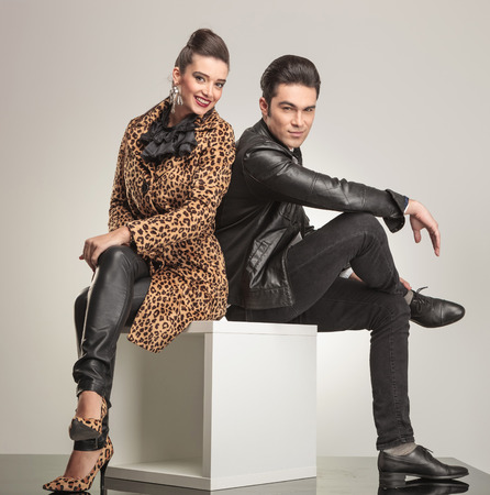 seated: Side view of young fashion couple sitting on a white cube holding their legs crossed. Stock Photo