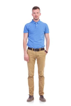 modelos hombres: Foto de longitud completa de un hombre joven ocasional celebraci�n de una mano en el bolsillo y mirando a la c�mara con una expresi�n seria. aislado en un fondo blanco
