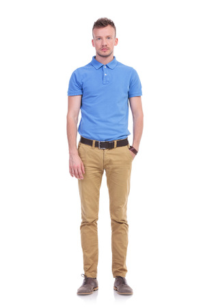 male hands: full length picture of a young casual man holding a hand in his pocket and looking into the camera with a serious expression. isolated on a white background