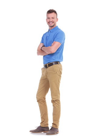 full length picture of a young casual man holding his arms crossed while looking into the camera. isolated on a white background