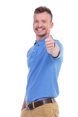 posing  agree: picture of a young casual man showing the thumb up gesture while smiling for the camera. isolated on a white background