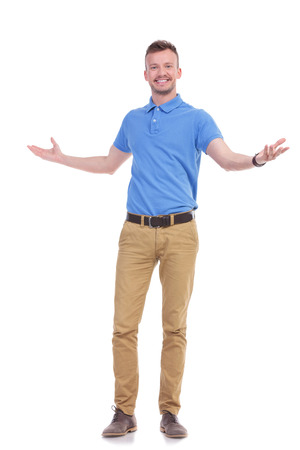 full length picture of a young casual man welcoming you with a smile on his face and his arms wide open. isolated on a white background photo