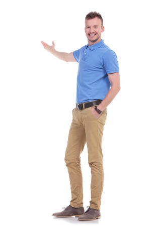 full length portrait of a young casual man presenting something in the back while holding a hand in his pocket and smiling for the camera. isolated on a white background Stockfoto