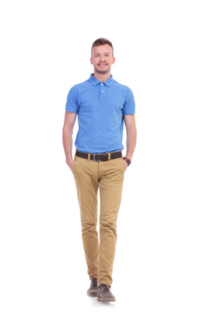 full length picture of a young casual man walking toward the camera with his hands in his pockets while smiling. isolated on a white background Stock Photo