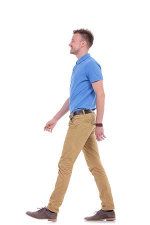 全長前方歩行とニコニコしながらカメラから離れて見るカジュアルな若者のビューの写真。白い背景に分離
