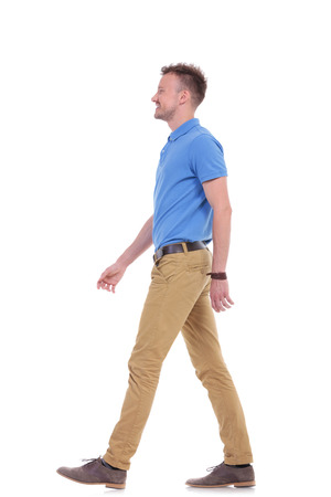 see side: full length side view picture of a young casual man walking forward and looking away from the camera while smiling. isolated on a white background