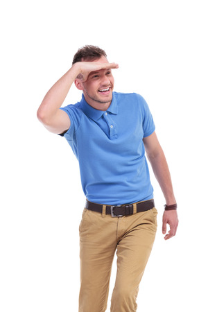 picture of a young casual man looking away and smiling while keeping his hand over his eyes to protect himself from the sun rays. isolated on a white background photo