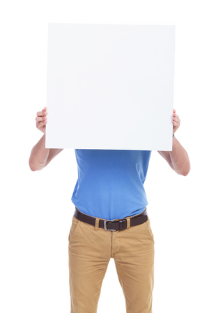 picture of a young casual man holding a blank board in front of his face. isolated on a white background photo