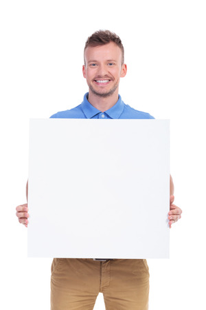 0picture of a young casual man holding a blank board with both hands and smiling for the camera. isolated on a white background