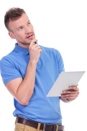 カジュアルな若者、手でタブレットを保持し、離れてしんみりと彼のもう一方の手を見て彼のあごの画像白い背景で隔離