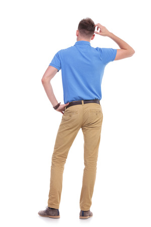 hands on waist: full length back view picture of a young casual man thinking while holding a hand on his waist and scratching his head with the other. isolated on a white background