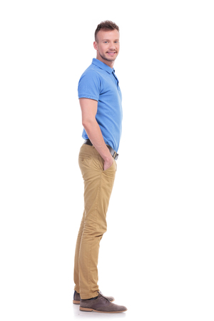 man side: full length side view picture of a young casual man looking into the camera while holding his hands inside his pockets and smiling. isolated on a white background Stock Photo