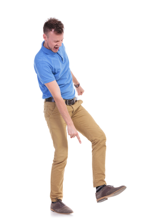 full length picture of a young casual man pointing angrily at the ground while holding his foot raised, on the point of stepping on something. isolated on a white background photo