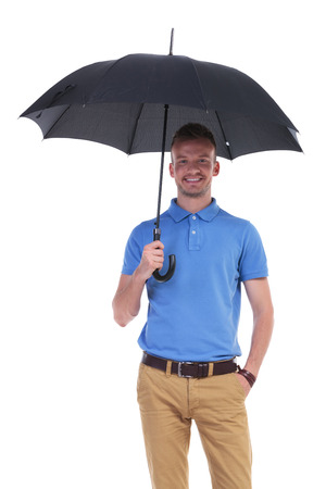 picture of a young casual man holding a black umbrella while holding his other hand in his pocket and smiling for the camera. isolated on a white background photo