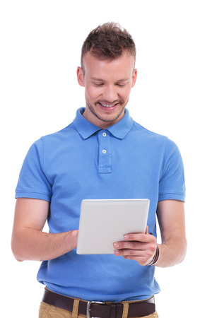 picture of a young casual man holding a tablet and looking at it with a smile on his face. isolated on a white background