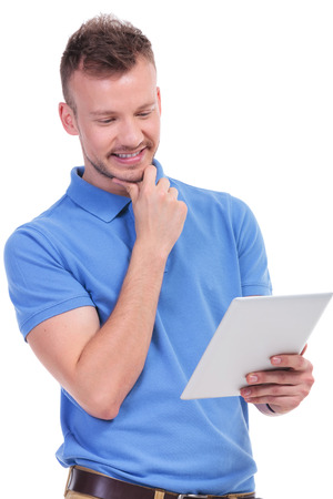 picture of a young casual man holding a tablet and looking pensively at it with a smile on his face. isolated on a white background