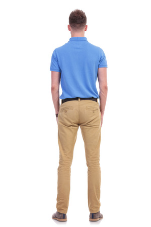 full length picture of a young casual man standing with his back at the camera. isolated on a white background