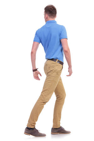 full length portrait of a young casual man turning away with his back towards the camera. isolated on a white background