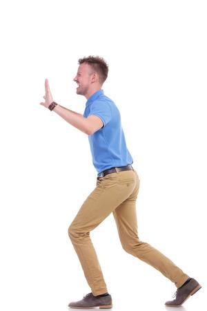 In voller Länge Seitenansicht Bild von einer jungen Casual Mann etwas drückt imaginären mit großen Schwierigkeiten. isoliert auf weißem Hintergrund Standard-Bild - 33450403