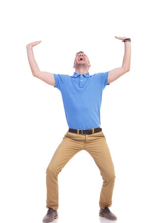 full length picture of a young casual man holding something imaginary above him with both hands and screaming out of difficulty. casual man being crushed. isolated on a white background photo