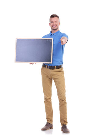 picture of a young casual man holding a blank blackboard and pointing at the camera with a smile on his face. isolated on a white background photo