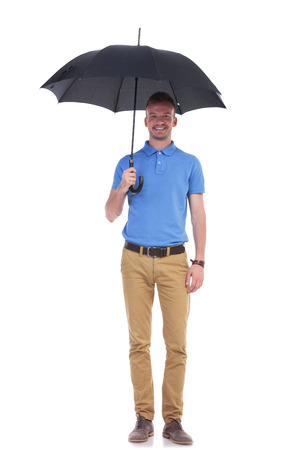 full length portrait of a young casual man holding a black umbrella and smiling for the camera. isolated on a white background photo