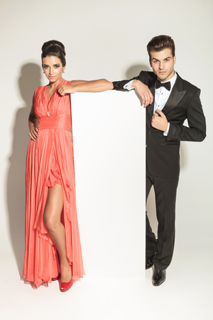 full suit: elegant fashion couple leaning on a white empy board, full body picture.
