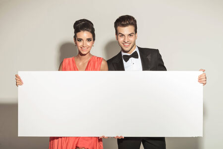 Fashion young elegant couple smiling while holding a white board. photo