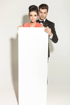 together with long tie: Elegant fashion couple holding a white empty board while smiling at the camera.